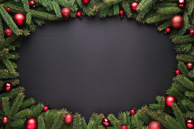 Kerstmis of nieuwjaar achtergrond. decoratief ovaal frame van dennentakken en kerstballen op een zwarte achtergrond