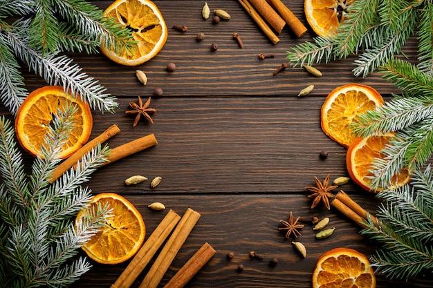 Kerstmis of nieuwjaar achtergrond. dennentakken met gedroogde sinaasappel, kardemom en glühwein kruiden