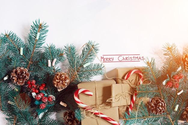Kerstmis of nieuwjaar achtergrond furtree takken geschenken decoratie op een witte achtergrond zon flare