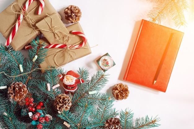 Kerstmis of nieuwjaar achtergrond furtree takken geschenken decoratie rood notitieboekje met pen op een witte ...