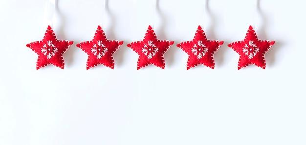 Kerstmis of nieuwjaar achtergrond met decor. rode zachte sterren met borduurwerk op witte achtergrond