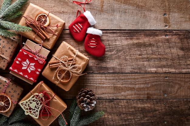 Kerstmis of nieuwjaar achtergrond met dennentakken, kerstballen, geschenkdoos, houten sneeuwvlokken en sterren op donkere houten achtergrond. plaats voor uw tekst