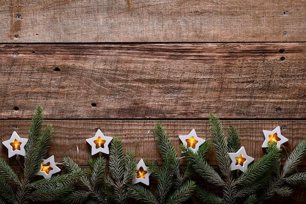 Kerstmis of nieuwjaar achtergrond met dennentakken, slinger, kerstballen, geschenkdoos, houten sneeuwvlokken en sterren op donkere houten achtergrond. plaats voor uw tekst