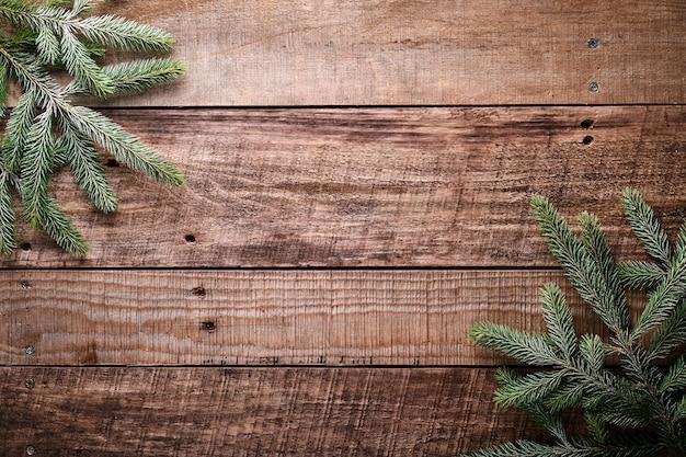 Kerstmis of nieuwjaar achtergrond met spar takken aan de rechter- en linkerkant op donkere houten achtergrond. plaats voor uw tekst