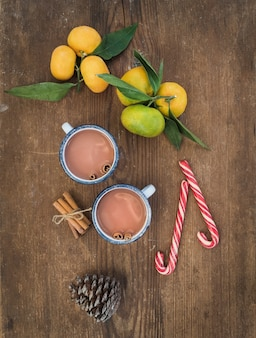 Kerstmis of nieuwjaar attributen. verse mandarijnen met bladeren, kaneelstokjes, dennenappel, warme chocolademelk in mokken en snoep stokken over rustieke houten tafel