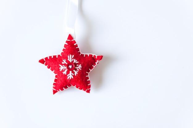 Kerstmis of nieuwjaar decor. rode zachte ster met borduurwerk op witte achtergrond