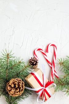 Kerstmis of nieuwjaar decoratieachtergrond met denneappels, dennentakken, geschenkdozen en snoep stokken