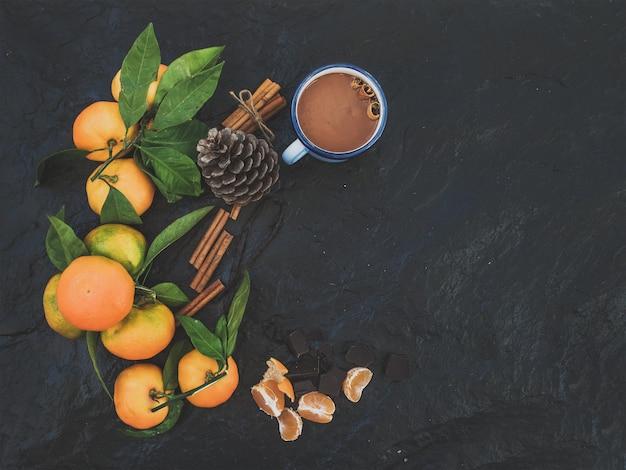 Kerstmis of nieuwjaar frame. verse mandarijnen met bladeren, kaneelstokjes, vanille, dennenappel en mok warme chocolademelk over donkere steen, bovenaanzicht