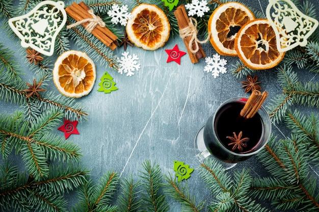 Kerstmis of nieuwjaar. grote tak van fit-tree met kegels, houten speelgoed, sneeuwvlokken en ingrediënten voor glühwein.