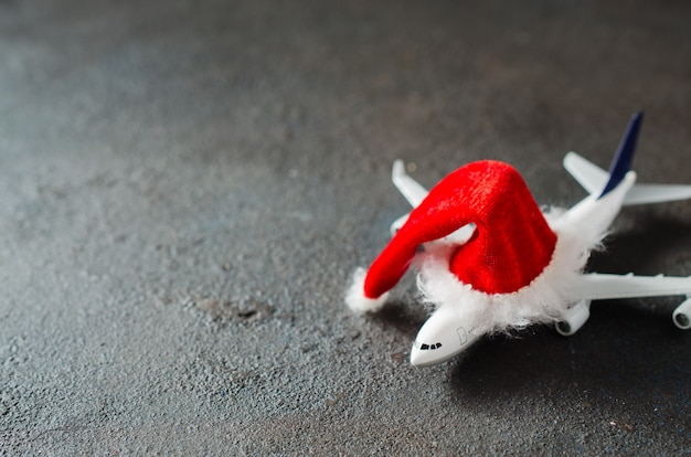 Kerstmis of nieuwjaar reizen concept. speelgoedvliegtuig en kerstman hoed.