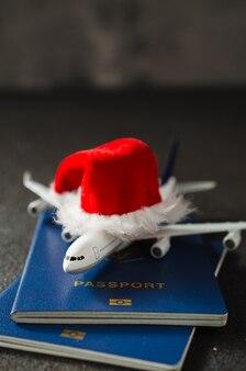 Kerstmis of nieuwjaar reizen concept. speelgoedvliegtuig met paspoorten en santa claus-hoed.