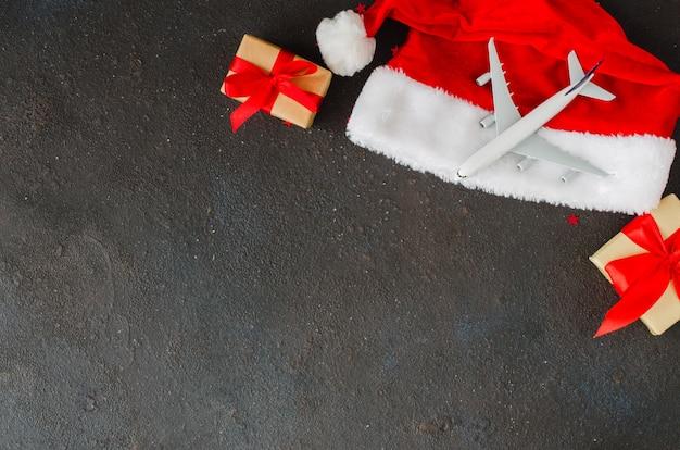 Kerstmis of nieuwjaar reizen concept. speelgoedvliegtuig op kerstmuts en geschenkdozen op donker beton.