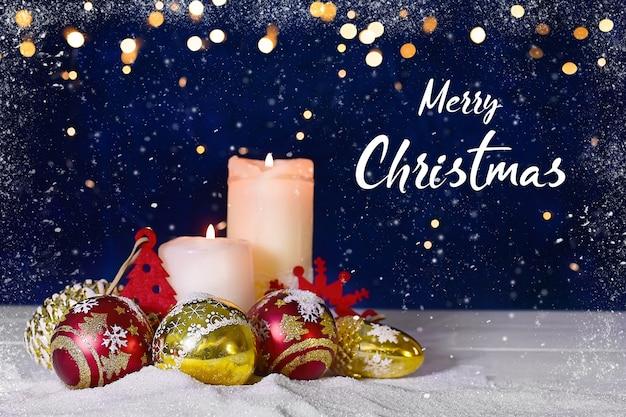 Kerstmis of nieuwjaar samenstelling van ballen kaarsen en ornamenten met heldere bokeh en sneeuw