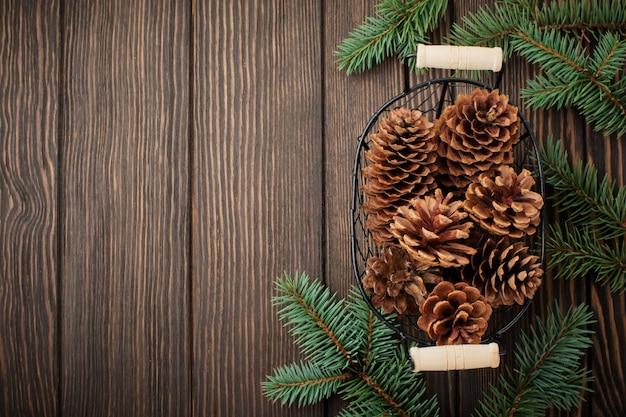 Kerstmis of nieuwjaar. sparrentakken, kerstboomspeelgoed, sterren, sneeuwvlok en kegels op donkerbruin houten.
