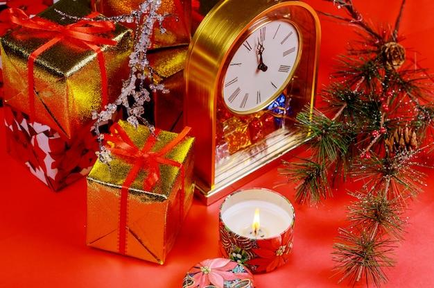 Kerstmis of nieuwjaarsamenstelling met rode kaars als achtergrond. twaalf uur. het concept van het nieuwe jaar.