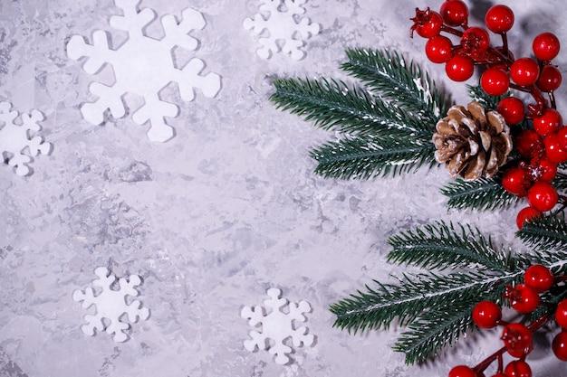 Kerstmis of winter samenstelling. grijze achtergrond met witte sneeuwvlokken en dennentakken. plat lag, bovenaanzicht