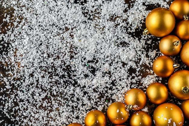 Kerstmis plat lag, nieuwjaar achtergrond. gouden kerstballen op donkere achtergrond, witte sneeuwvlokken.
