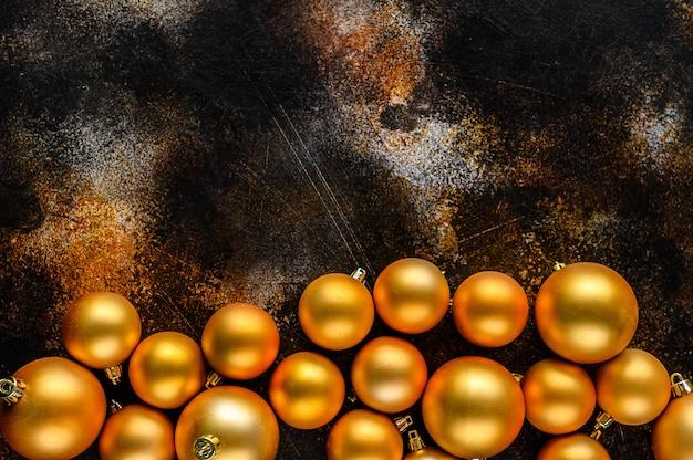 Kerstmis plat lag, nieuwjaar achtergrond. gouden kerstballen op donkere achtergrond.