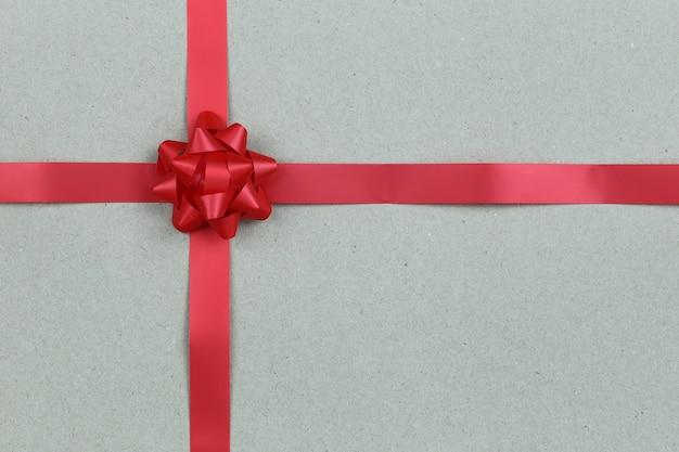 Kerstmis red bow en lint op bruine papieren achtergrond.