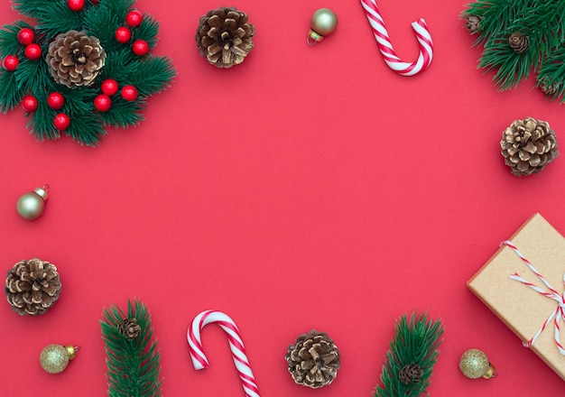 Kerstmis rode achtergrond met twee zuurstokken, de kroon van kerstmis met bessen, geschenkdoos, fir kegels.