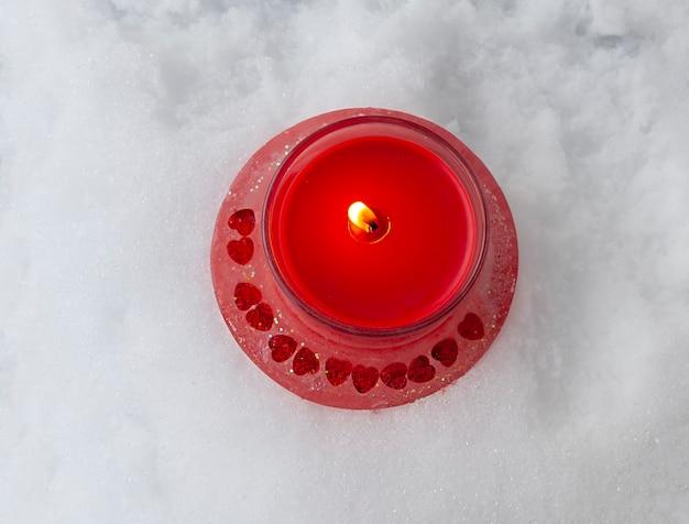 Kerstmis rode brandende kaars in de transparante glazen kandelaar op sneeuw achtergrond