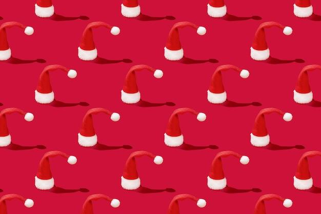 Kerstmis rode kerstman hoed op rode achtergrond. nieuwjaar of kerstmis abstract patroon.