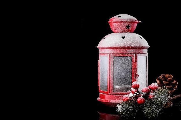 Kerstmis rode lantaarn op sneeuw met fir branch op zwarte achtergrond. winter decoratie achtergrond