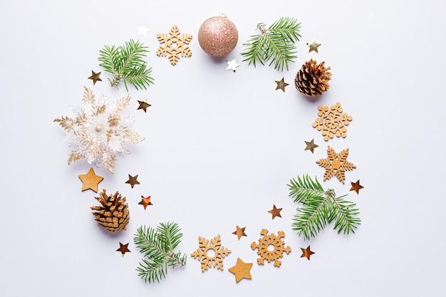 Kerstmis rond frame met dennentakken, dennenappels, confetti op grijs, kopie ruimte.
