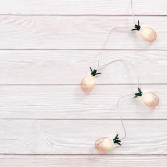 Kerstmis rustieke achtergrond met koordlichten als gouden ananas gekleurd op houten. nieuwjaar fairy garland.