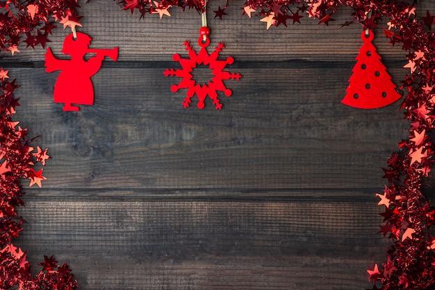 Kerstmis rustieke houten achtergrond met rode stuk speelgoed decoratie en klatergoud met sterren
