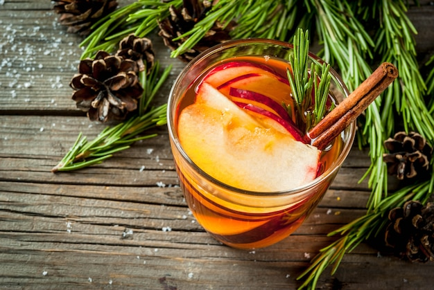 Kerstmis, thanksgiving-drankjes. herfst, wintercocktail, warme sangria, glühwein - appel, rozemarijn, kaneel, anijs. op oude rustieke houten tafel. met kegels, rozemarijn. kopieer ruimte