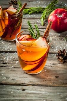 Kerstmis, thanksgiving-drankjes. herfst, wintercocktail, warme sangria, glühwein - appel, rozemarijn, kaneel, anijs. op oude rustieke houten tafel. met kegels, rozemarijntakken. kopieer ruimte