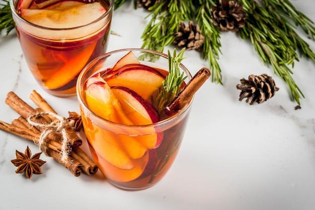 Kerstmis, thanksgiving-drankjes. herfst, wintercocktail, warme sangria, glühwein - appel, rozemarijn, kaneel, anijs. op witte marmeren tafel. met kegels, rozemarijn. kopieer ruimte