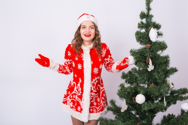 Kerstmis, vakantie en emotiesconcept - verraste kerstmanvrouw dichtbij kerstboom op witte muur.