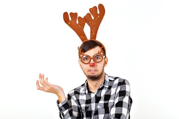 Kerstmis, vakantie en grappig concept - man met herten hoorns en rudolf nous op witte muur