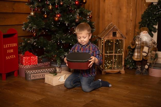 Kerstmis, vakantie en jeugdconcept - glimlachende jongen met giftdoos thuis