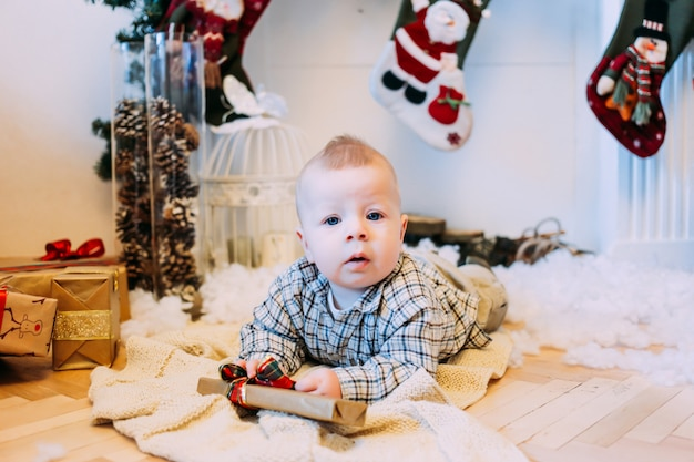 Kerstmis, vakantie en kinderjarenconcept - jongen met giftdoos thuis