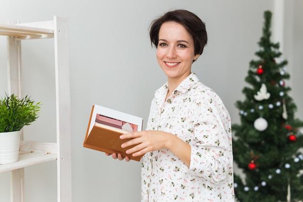 Kerstmis, vakantie en mensenconcept - het gelukkige boek van de vrouwenlezing thuis.
