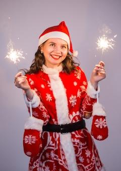 Kerstmis, vakantie en mensenconcept - vrouw in santakostuum met lichten en schittert het lachen.