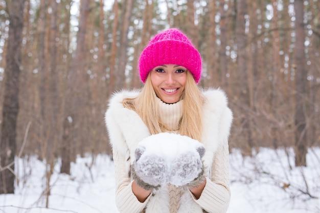 Kerstmis, vakantie en seizoenconcept - de jonge mooie glimlachende sneeuw van de vrouwenholding dient binnen in