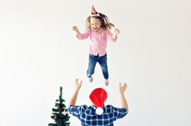 Kerstmis, vakantie en vaderschap concept - grappige vader met kerstmuts gooit zijn dochter op een witte achtergrond met kopieerruimte.