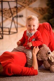 Kerstmis, vakantie, familie en mensenconcept - gelukkige moeder en kind spelen thuis