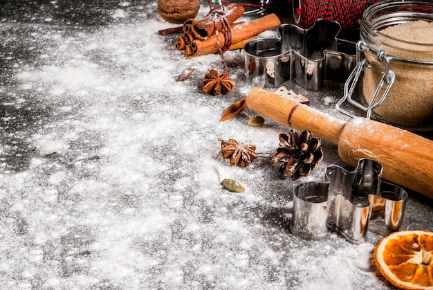 Kerstmis, vakantie koken. ingrediënten, kruiden, gedroogde sinaasappels en bakvormen, kerstdecoraties (ballen, firtree tak, kegels), op zwarte stenen tafel,