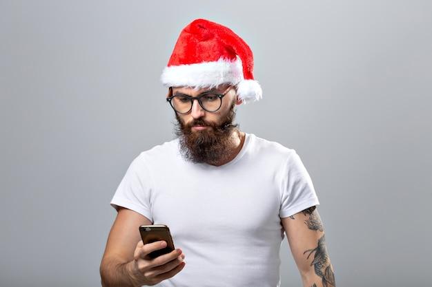 Kerstmis, vakantie, technologie en mensen concept - knappe bebaarde man in kerstmuts selfie foto met smartphone op grijze achtergrond.