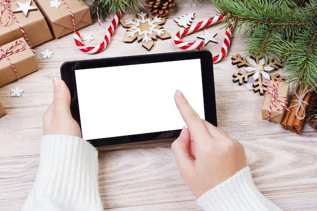 Kerstmis van vrouwelijke handen gebruikt geopende tablet op rustieke houten die lijst met kerstmisdecoratie wordt behandeld, hoogste vlakke mening, legt