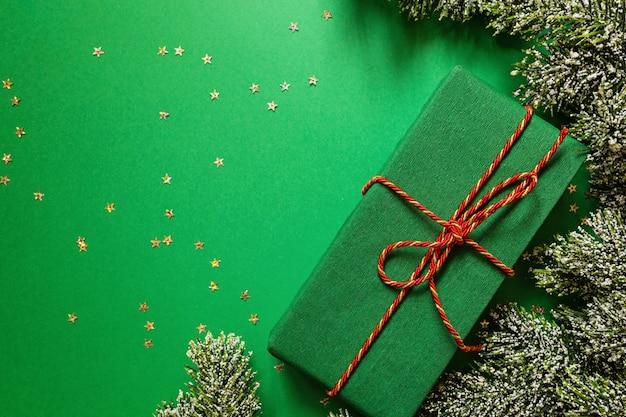 Kerstmis verpakte geschenkdoos en boomtakken op groene achtergrond met confetti. nieuw jaar concept. wenskaart, xmas viering 2020. plat lag, sjabloon, bovenaanzicht, kopie ruimte