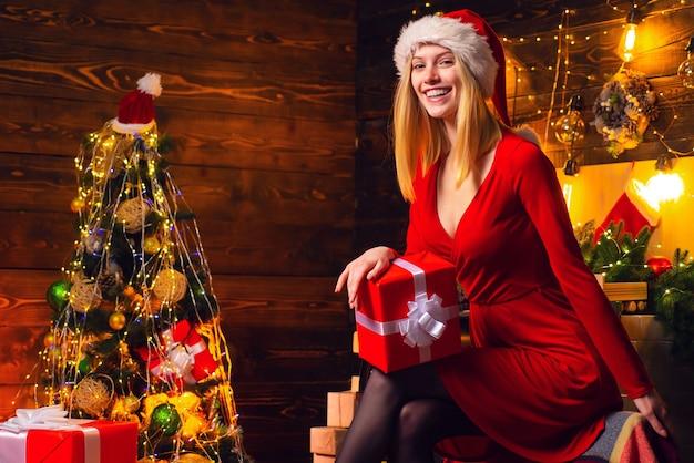 Kerstmis vieren. vrolijke dame in kerstfeest jurk. gelukkig nieuwjaarsfeest. vrouw elegante meisje rode jurk kerstmis vieren. meisje in de buurt van kerstboom winter decoraties interieur.