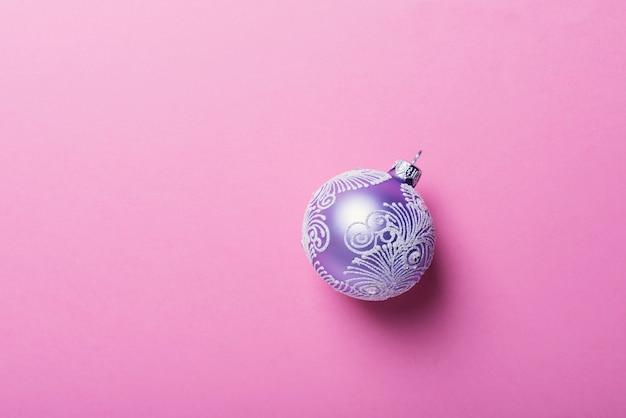 Kerstmis violette bal op de roze achtergrond, kerstmisconcept. bovenaanzicht met kopie ruimte voor tekst