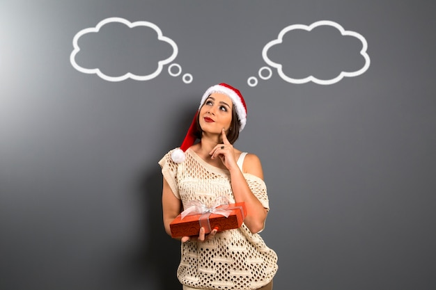 Kerstmis vrouw opzoeken lege kopie ruimte houden geschenkdoos aanwezig, jonge gelukkige glimlach vrouw draagt kerstman hoed, aantrekkelijk nieuwjaarsfeest meisje, over bord met lege ballons