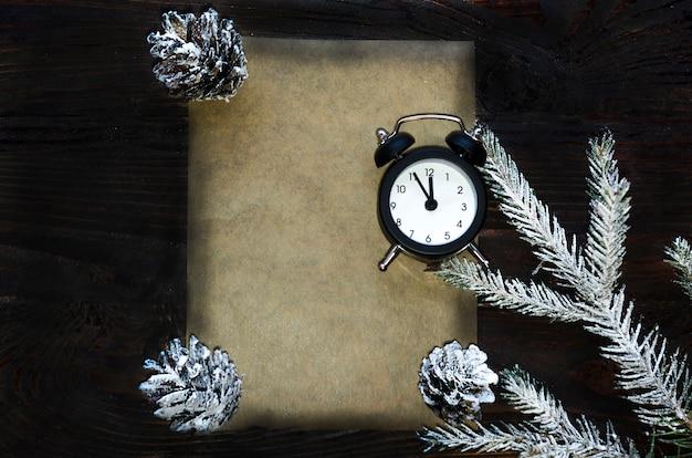 Kerstmis vuren tak met kegels, 12 uur, horloge op donkere houten achtergrond, brief aan de kerstman. copyspace